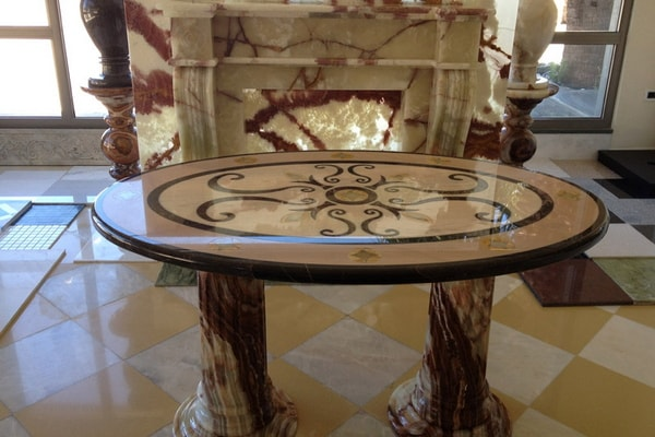 Waterjet table design from Portogalo, Nero Marquina and Onyx and fireplace from Onyx